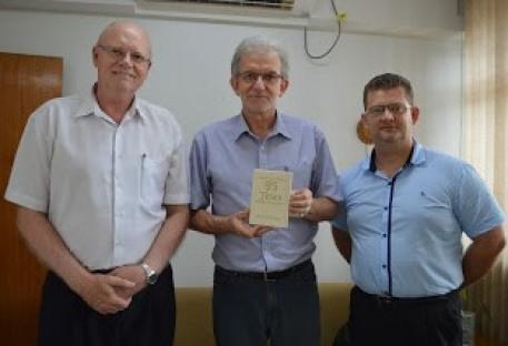 """Editora Sinodal presenteia o Pastor Presidente Nestor Paulo Friedrich, da IECLB, com a obra """"95 Teses"""", de Martim Lutero."""